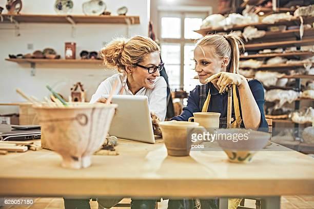 Potter entrepreneur using digital tablet  in workshop