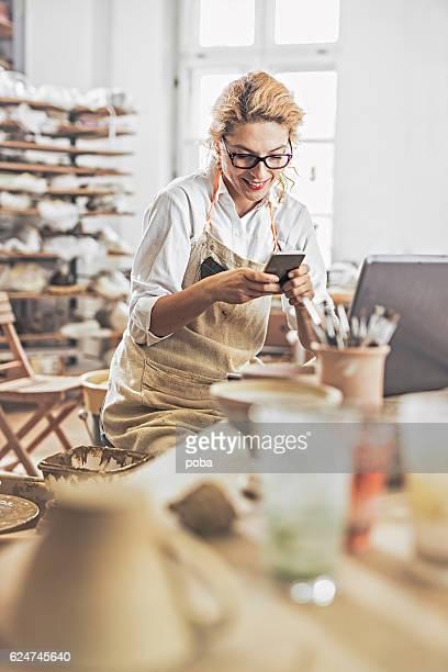 Potter entrepreneur using laptop and mobile phone  in workshop