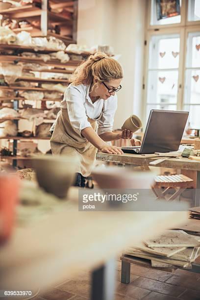 Potter entrepreneur using laptop  in workshop