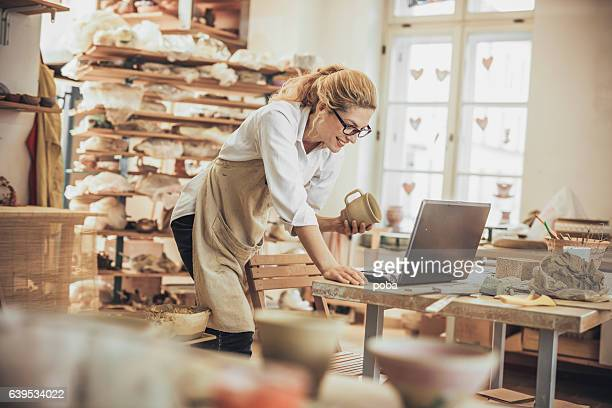 potter entrepreneur using laptop  in workshop - craftsman stock photos and pictures
