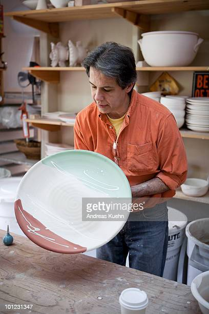 Potter holding a big plate for glazing.