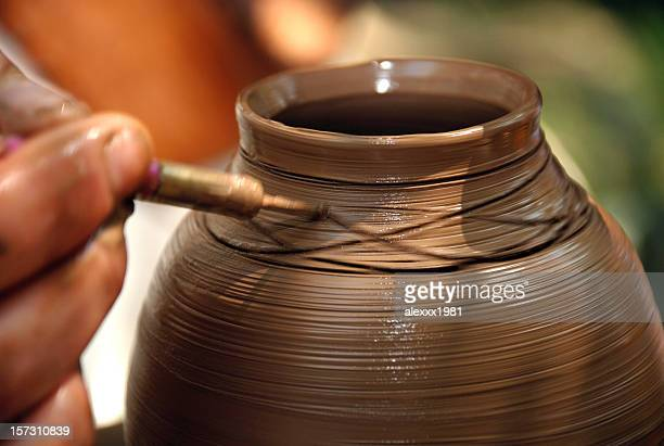 potter inflicts a decorative pattern on spinning pot