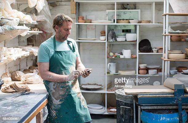 Potter looking at smart phone in his studio