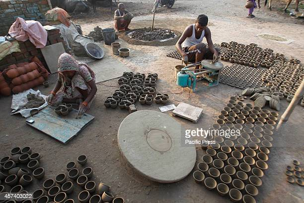 A potter makes an earthen lamps called 'Diya' to be sold before the Diwali Festival at Allahabad