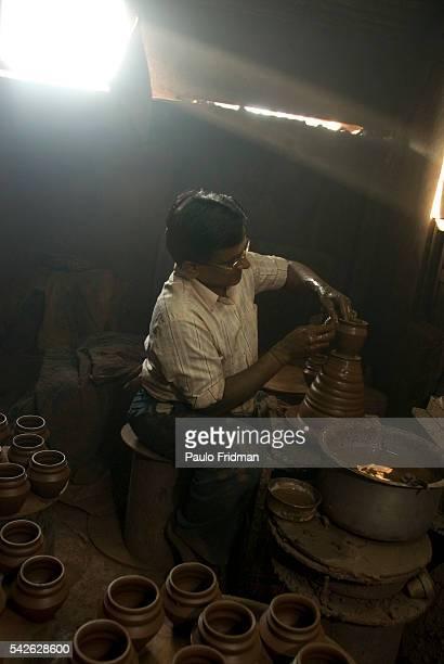 A potter makes handmade pots in Dharavi Asia's biggest slum in Mumbai Maharastra India