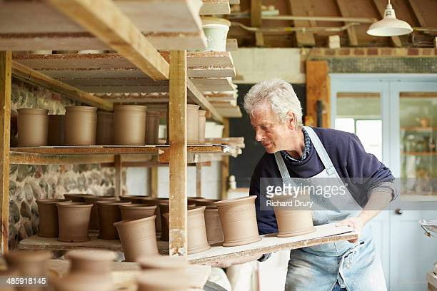 Potter moving boards of pots