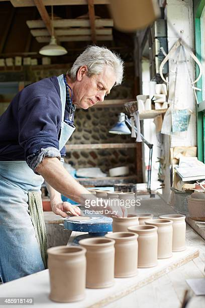 Potter processing small store jars