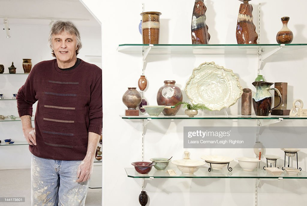 Potter standing in gallery with finished pieces. : Stock Photo
