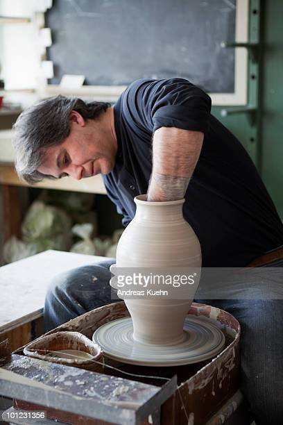 Potter throwing clay on pottery wheel.