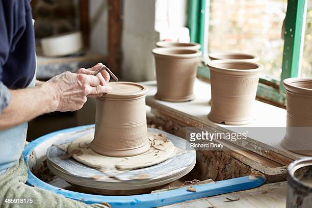 potter turning the footring of a cutlery drainer - richard drury stock pictures, royalty-free photos & images