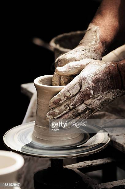 A potters dirty hands turning a beaker on a potter wheel