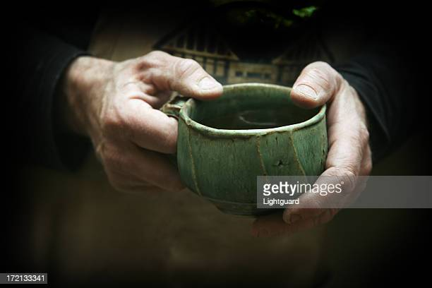 potter's hands hold handmade pottery mug