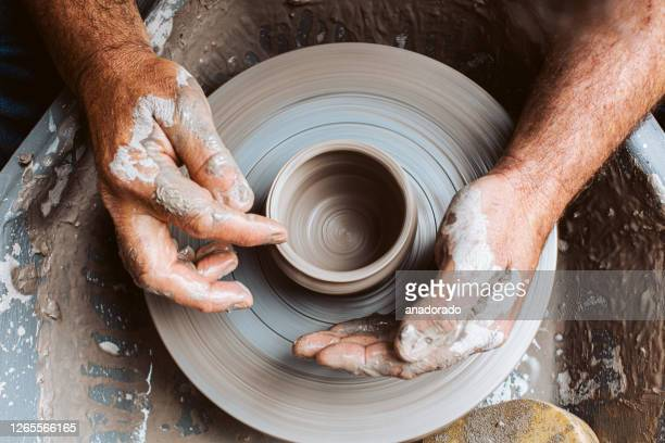 potter's hands working clay on a potter's wheel - craftsperson stock pictures, royalty-free photos & images