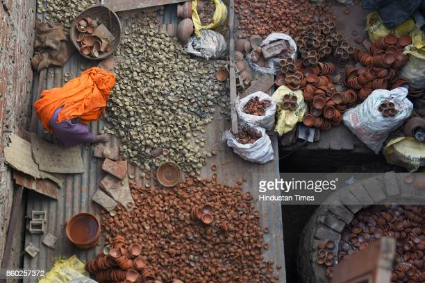 Potters in West Delhi's Uttam Nagar are busy in making earthen diyas and other decorative items for the upcoming Diwali festival, on October 3, 2017...