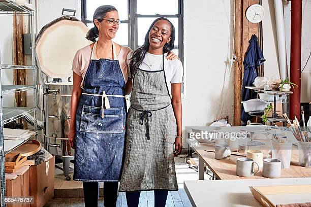 Potters in workshop wearing aprons smiling