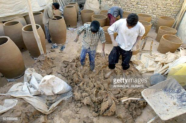 Potters step on clay as their colleagues make traditionnal ovens out of it in the background 08 February 2005 in the holy Shiite city of Najaf those...