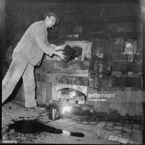 Pottery worker StokeonTrent Staffordshire 19651968 A man tending the fire beneath a kiln at an unidentified pottery works Artist Eileen Deste