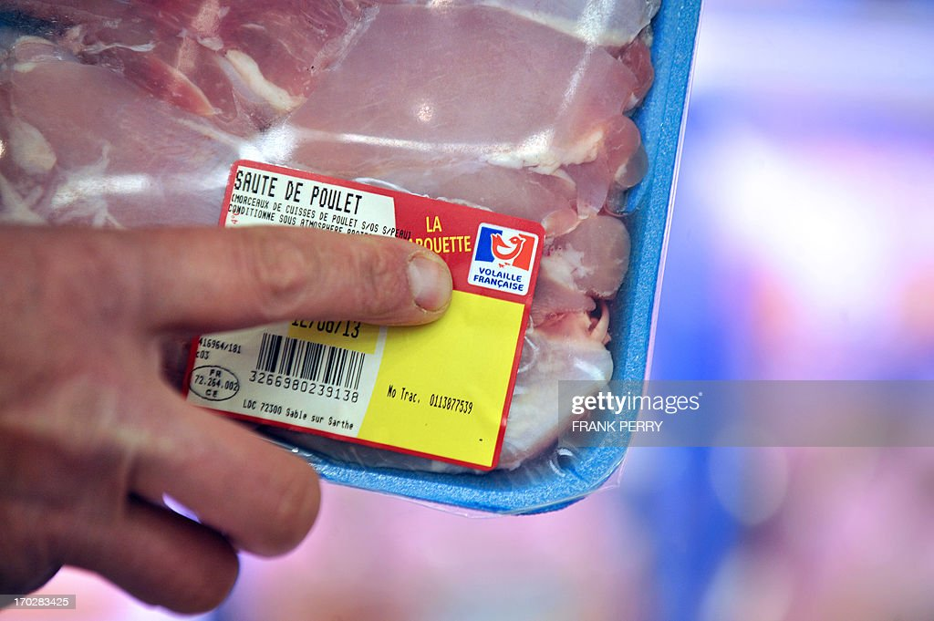 A poultry farmer, member of the French FNSEA union, shows chicken meat with the French label 'Volailles Francaise' in a Leclerc supermarket during a demonstration against meat from foreign countries on June 10, 2013 in Saint-Herblain, near Nantes.