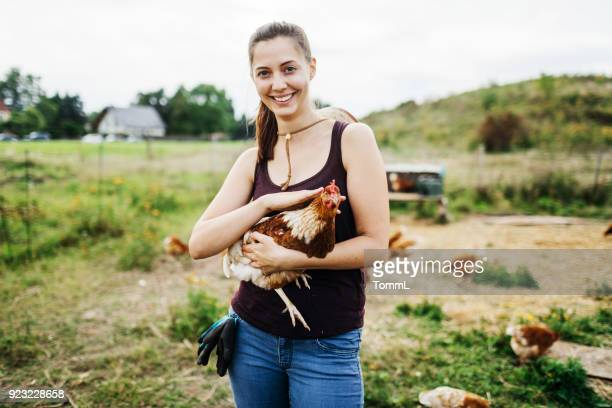 Poultry Farmer Smiling Holding Chicken While Working
