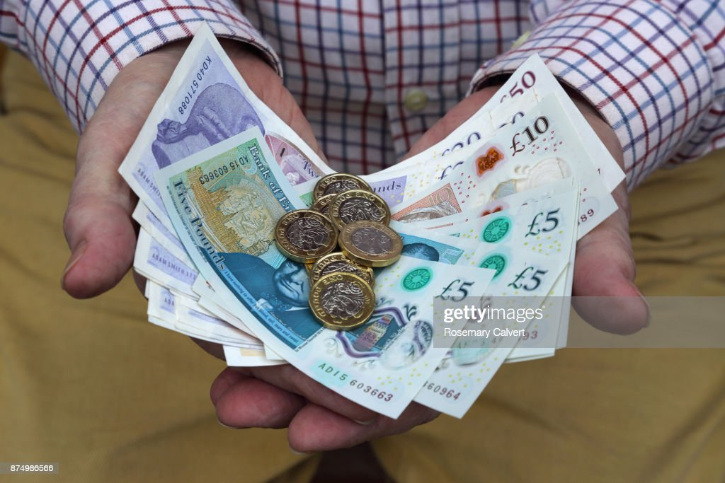 Pound coins and British pound notes in man's hands. : Stock Photo