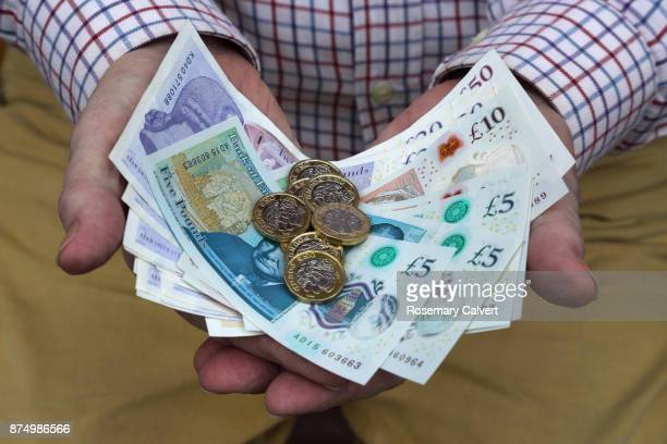 pound coins and british pound notes in man's hands. - british pound sterling note stock pictures, royalty-free photos & images