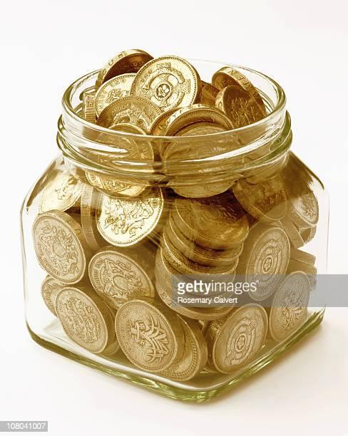 Pound coins filling jam jar.