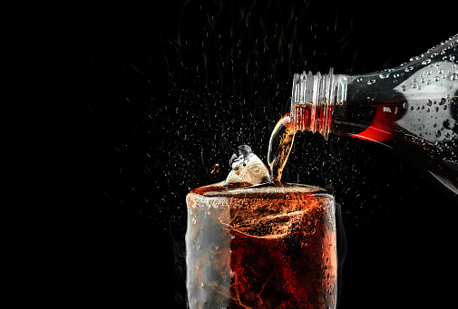 Pour soft drink in glass with ice splash on dark background. 1062831310