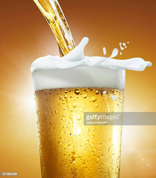 Pouring a glass of beer with foam overflowing.