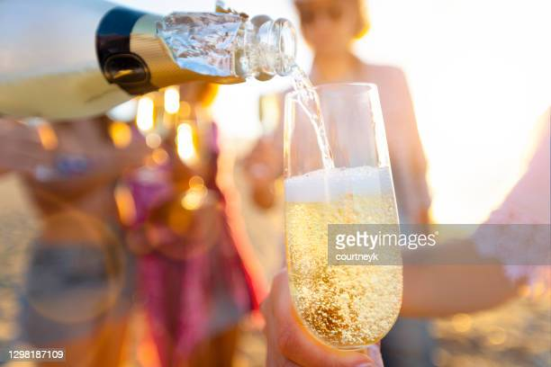 pouring a glass of champagne with people partying in the background. - honour stock pictures, royalty-free photos & images