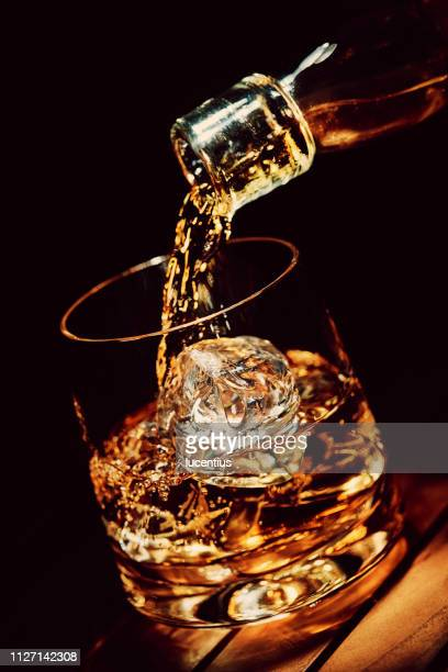 pouring a glass of whiskey on ice - whisky stock photos and pictures