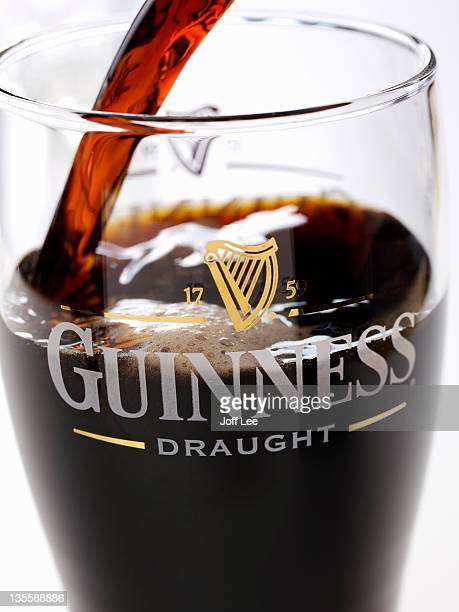 pouring a pint of guinness - guinness stock pictures, royalty-free photos & images