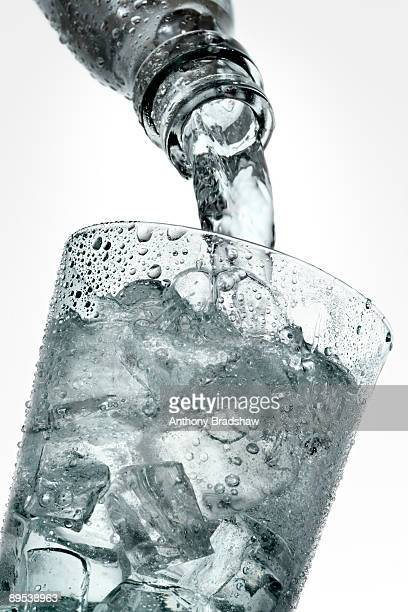 pouring a refreshing drink into a glass of ice - soda bottle stock photos and pictures