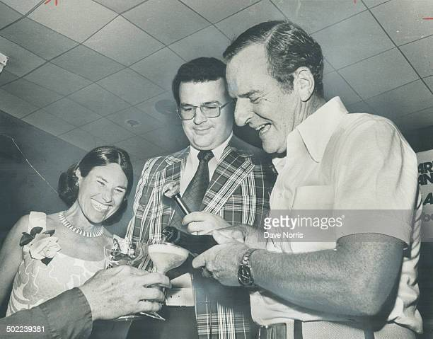 Pouring a toast, Barney Danson, the Liberal who defeated uranium millionaire Stephen Roman in York North riding, stands on the victory platform with...