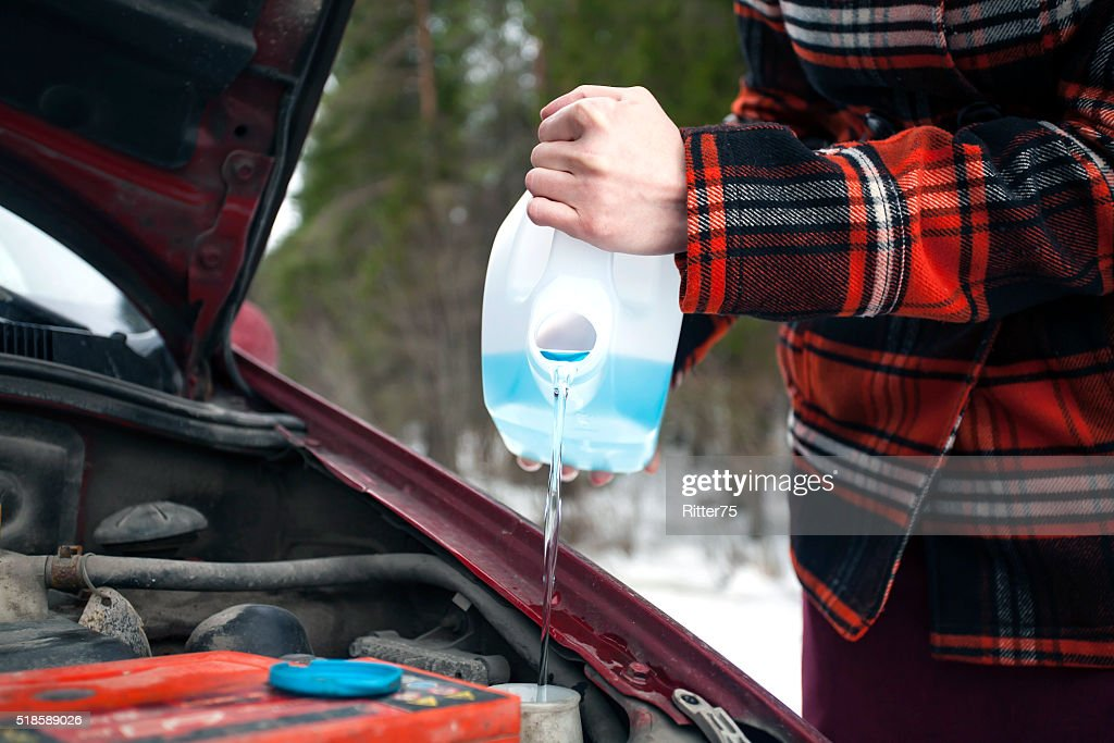 Pouring Antifreeze Washer Fluid into Windshield Washer Tank : Stock Photo