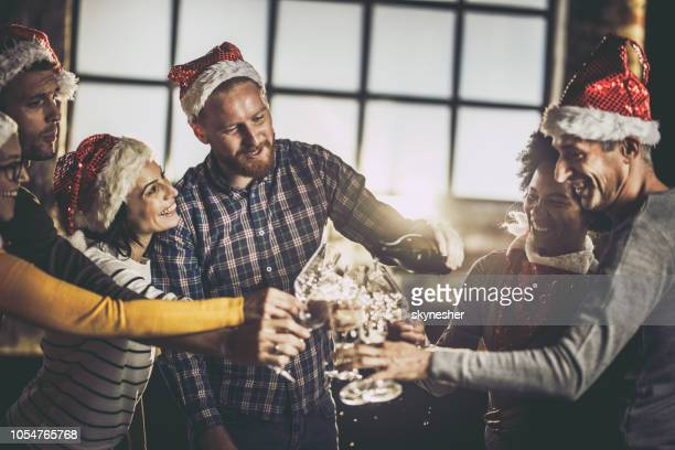 pouring champagne on christmas office party! - work party stock pictures, royalty-free photos & images
