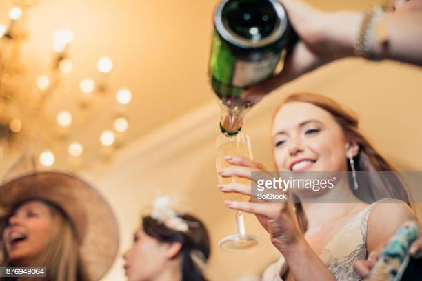 pouring champagne with friends - fascinator stock pictures, royalty-free photos & images