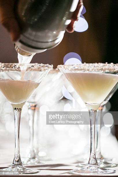 Pouring cocktail glasses at night with salt rim