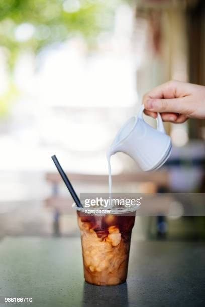 pouring cream in cold brew coffee - iced coffee stock pictures, royalty-free photos & images