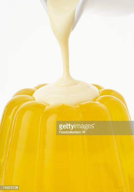 Pouring custard over lemon jelly