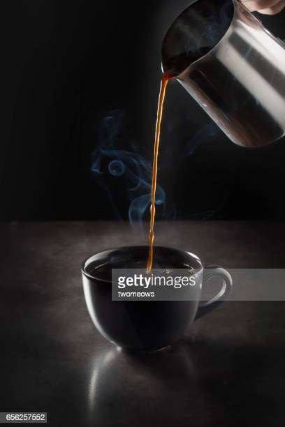 Pouring espresso to back coffee cup on black background.