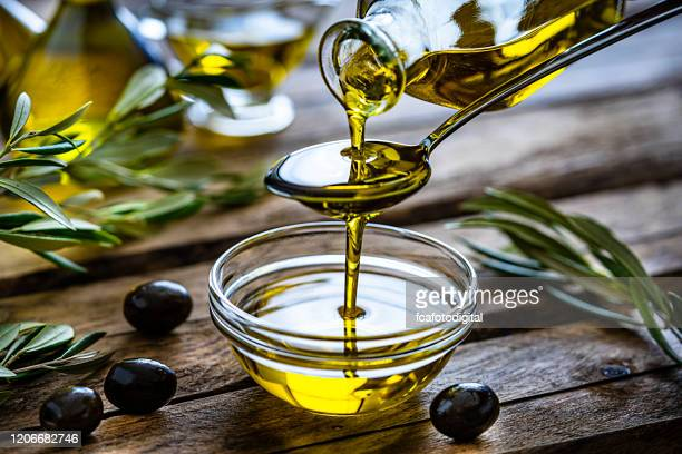 pouring extra virgin olive oil in a glass bowl - olive oil stock pictures, royalty-free photos & images