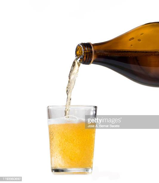 pouring glass of beer from bottle on a white background. - ラガービール ストックフォトと画像