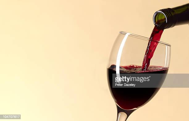 pouring glass of red wine with copy space - vin photos et images de collection
