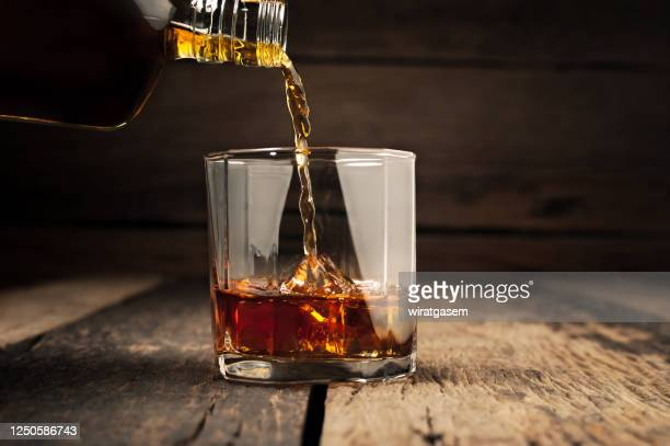 pouring glass of whiskey, close-up whisky on the rocks. - bourbon whiskey stock pictures, royalty-free photos & images