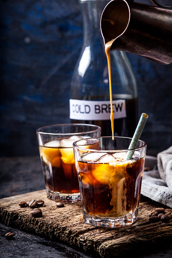 Pouring homemade vanilla flavoured coffee creamer into a glas with iced coffee - gettyimageskorea