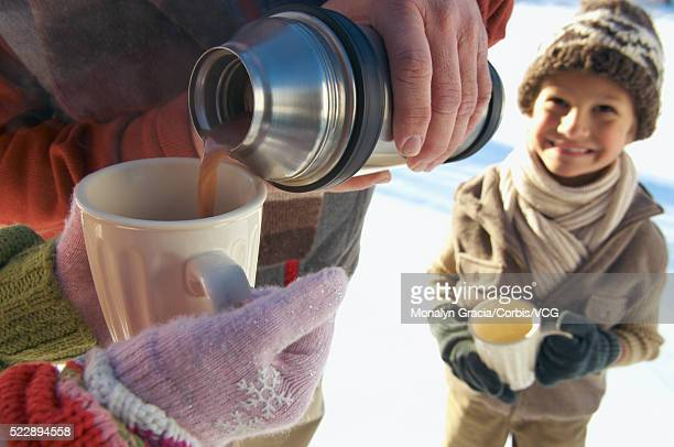 Pouring hot chocolate from a thermos