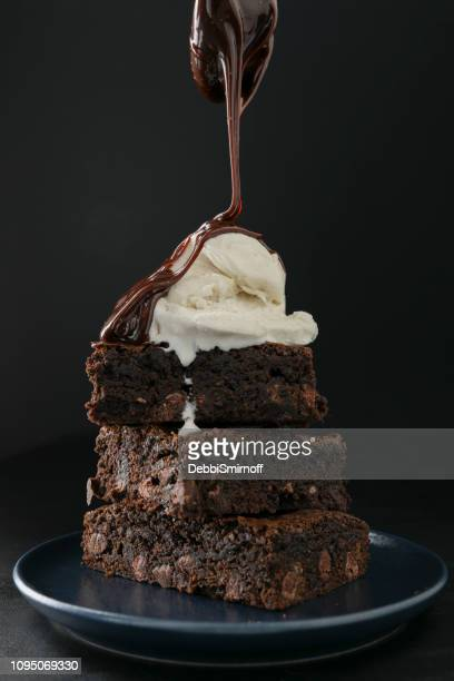 pouring hot fudge on brownies - dessert topping stock pictures, royalty-free photos & images