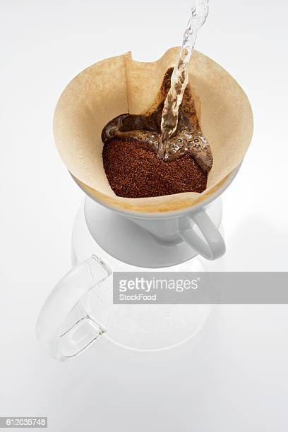 pouring hot water onto ground coffee in filter - ground coffee stock photos and pictures