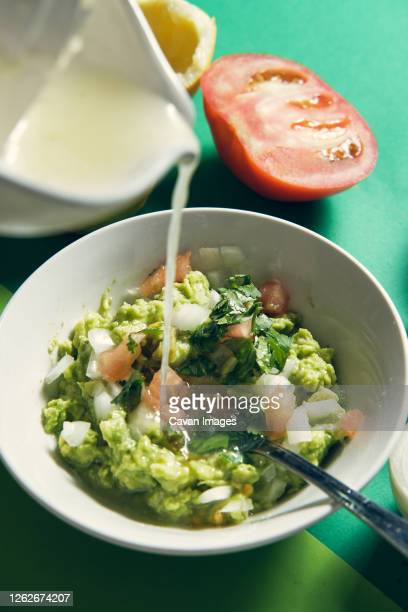 pouring in the lime juice to finish making the guacamole sauce - stamppot stockfoto's en -beelden