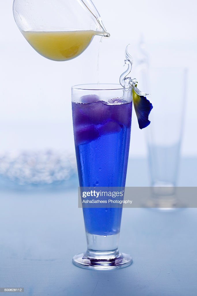Pouring lemon juice on Butterfly pea drink : Stock Photo